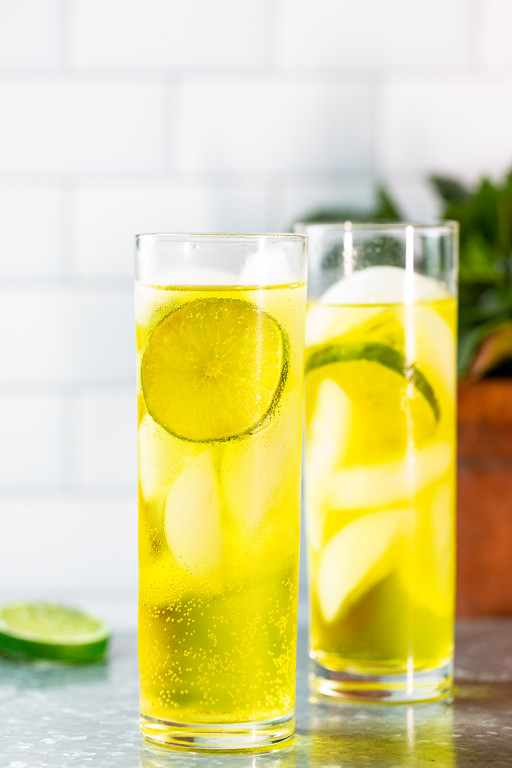 Two tall glasses filled with a bright yellow cocktail and garnished with a lime wheel.