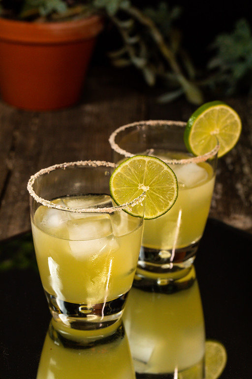 Two glasses rimmed with salt, garnished with lime and filled with a margarita.