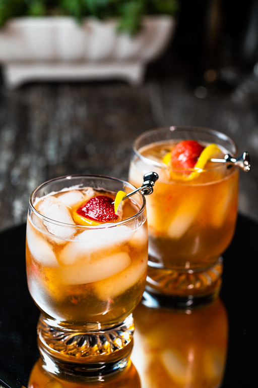 Two cocktails garnished with strawberry and lemon.