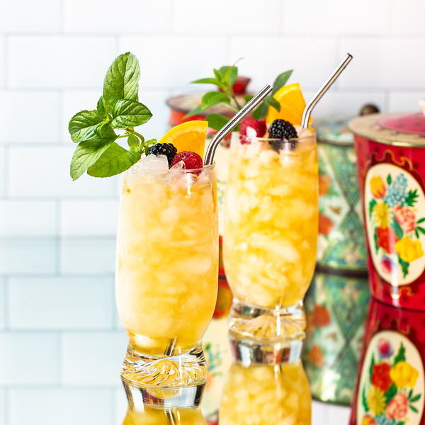 Two bright yellow cocktails garnished with mint, blackberries, raspberries, and an orange slice.