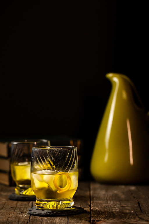 Two glasses of a bright yellow cocktail with a pitcher behind them.