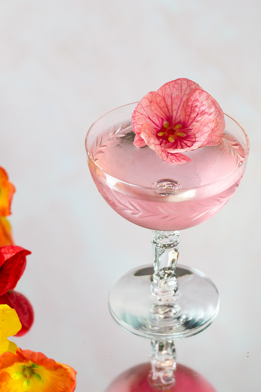 Pretty pink cocktail garnished with a pink flower.