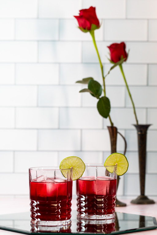 Two cocktail glasses filled with a deep red cocktail and garnished with a lime wedge.