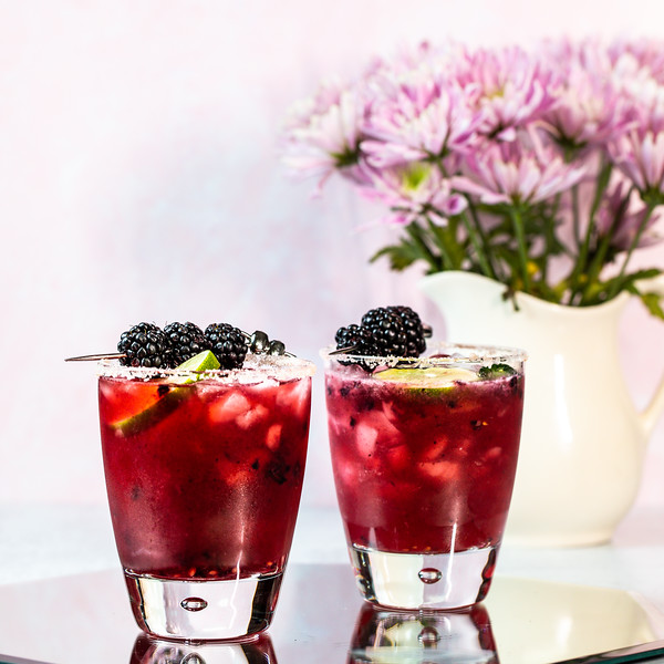 Two cocktail glasses filled with deep purple cocktail garnished with a lime wheel and blackberries.