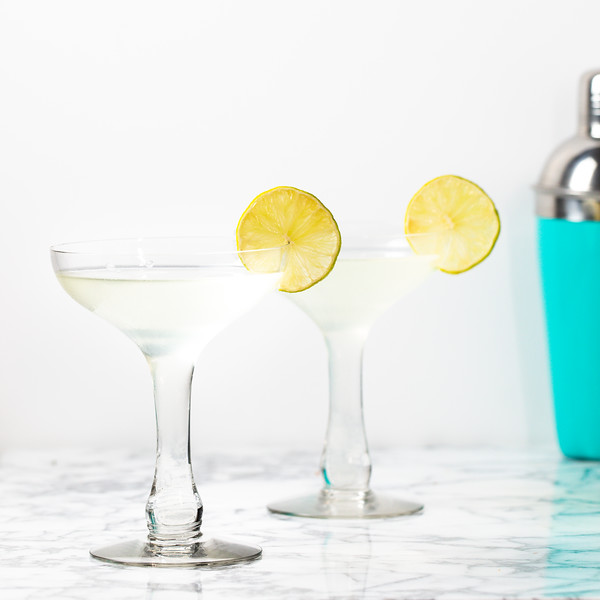 Two coupe glasses filled with a clear cocktail and a lime wheel.