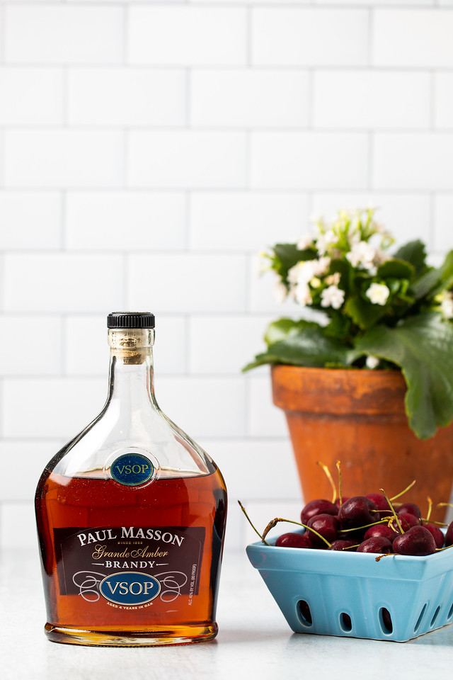 A bottle of brandy and a container of cherries.