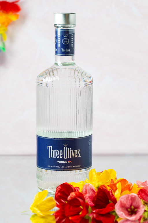 Bottle of Three Olives Vodka and hibiscus flowers.