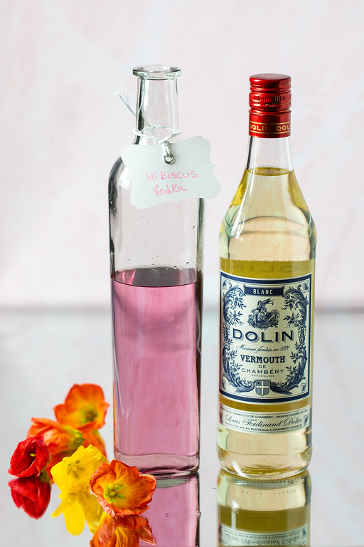 Hibiscus vodka and vermouth on a mirrored surface with hibiscus flowers.