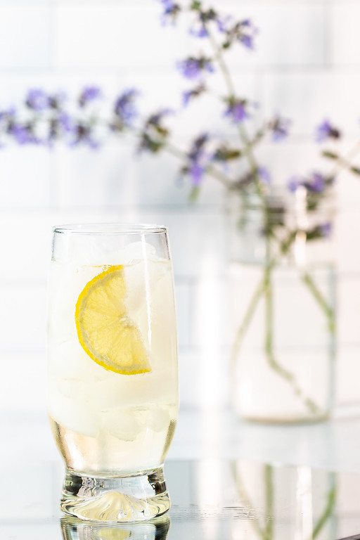 Light colored cocktail in a glass with a lemon wedge and a vase of purple flowers in the background.