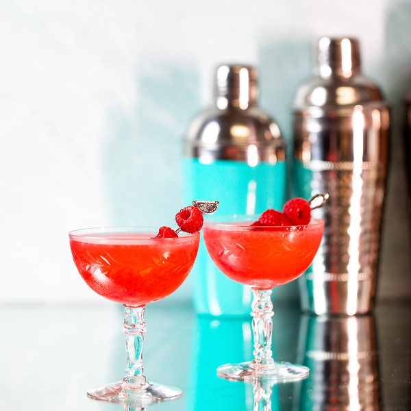 Two bright red cocktails garnished with raspberries in front of two cocktail shakers.