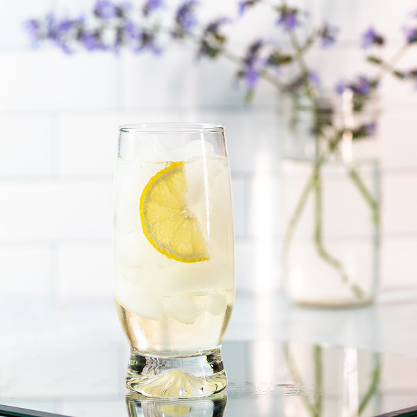 Cocktail glass filled with a light colored cocktail, garnished with a lemon slice with a vase of purple flowers behind it.