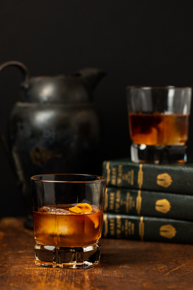 Dark brown cocktail with an orange twist in front of some vintage books.