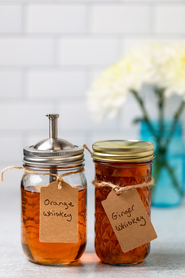Two mason jars, one with orange whiskey and one with ginger whiskey.