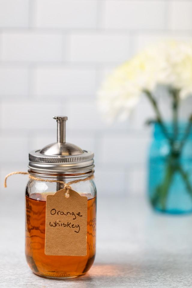 "Jar of brownish-orange liquid with tag reading ""orange whiskey."""