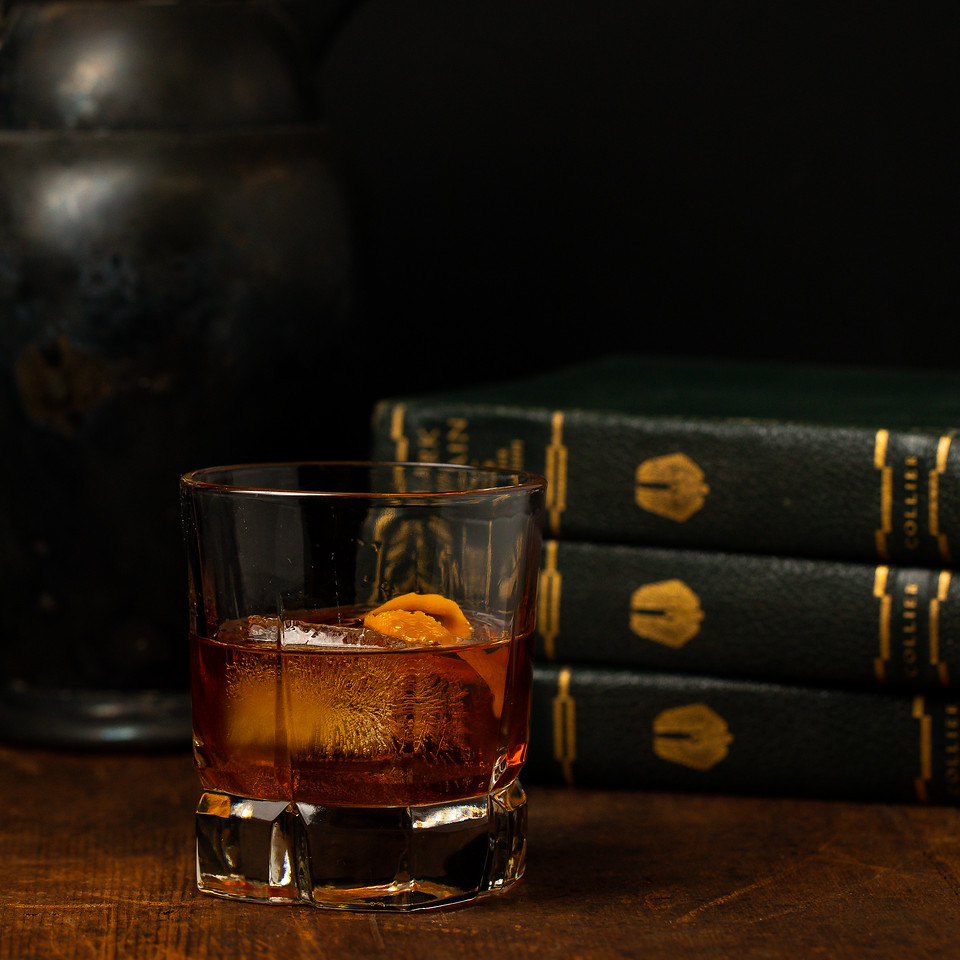 Bourbon old fashioned in a cocktail glass in front of vintage books and pitcher.