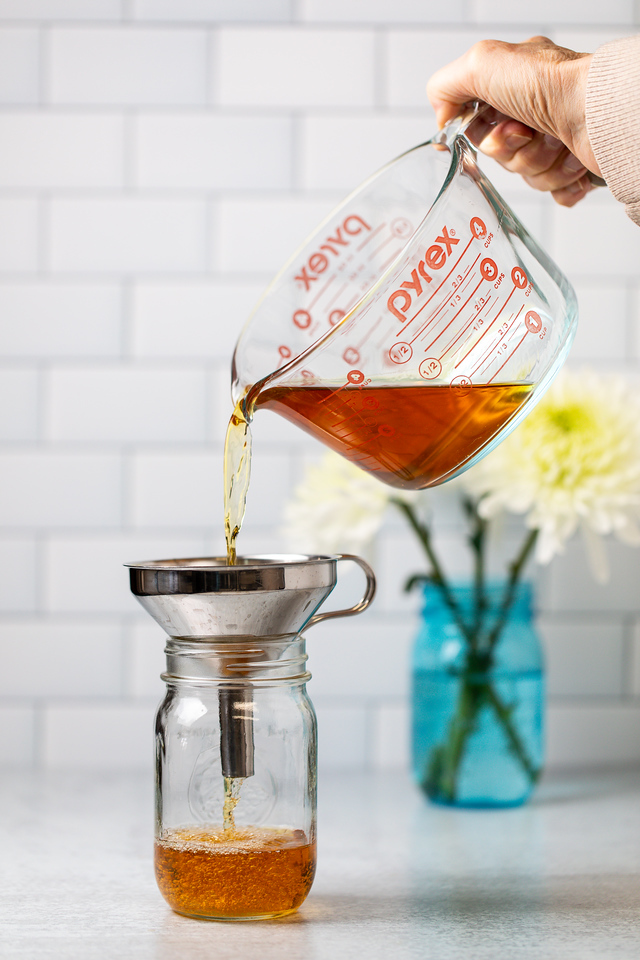 Orange whiskey being poured into a mason jar.