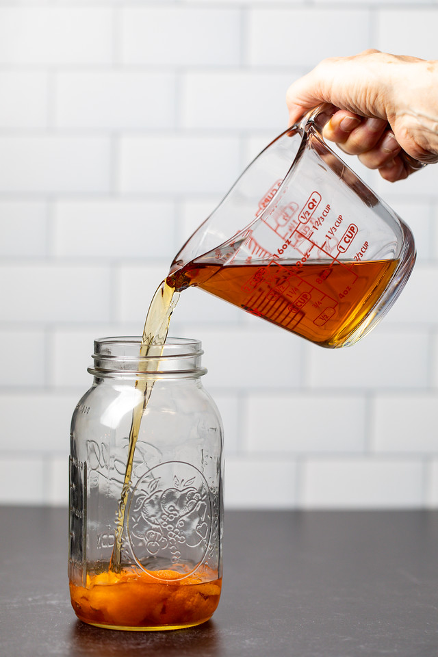 Mason jar with orange peels being filled with whiskey.