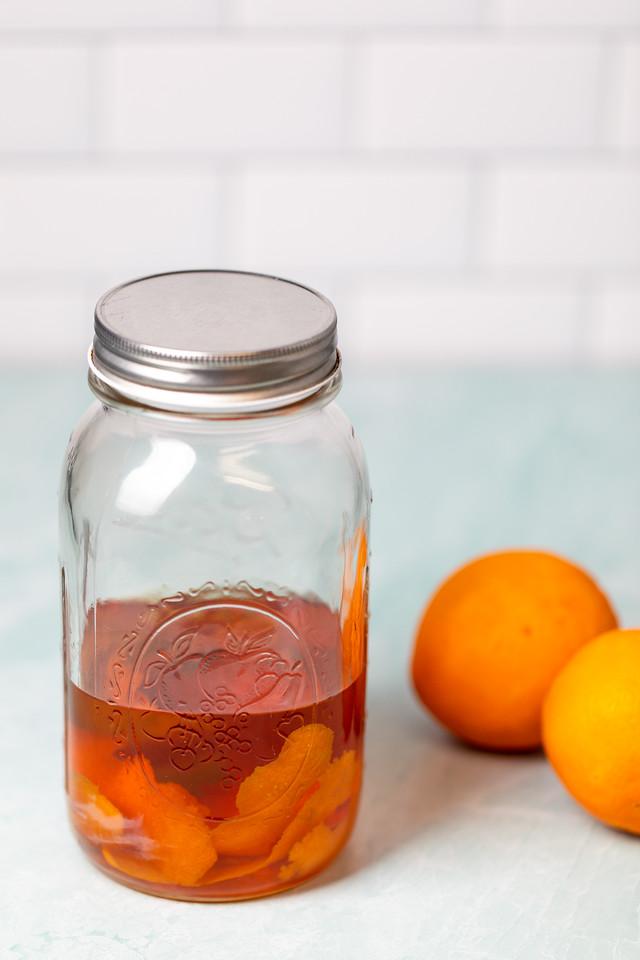 Mason jar half filled with orange peels and whiskey.
