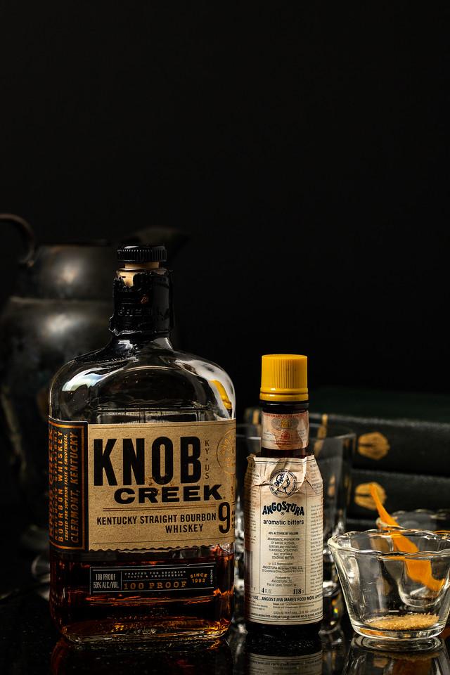 Bottle of Knob Creek, Angostura bitters, sugar and an orange peel.