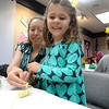 Courtesy Mentor Public Library | Kelsey Speck makes a necklace out of honeycomb cereal, because one can never have too much honey at a Winnie-the-Pooh tea party.