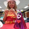 Courtesy Mentor Public Library | Alexis Damren makes a party hat at Mentor Public Library's tea party, even though she already brought a snazzy hat with her.