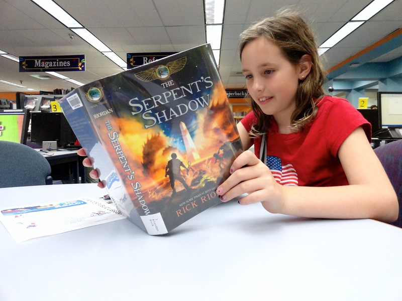 Courtesy Mentor Library | Abby Horvath is so excited about summer reading that she doesn't want to wait until she gets home to start.