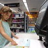 Courtesy Mentor Library | Olivia Conn checks out her first batch of books for summer reading.