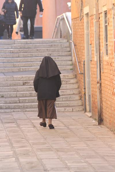Nun walking down alleyway in Venice