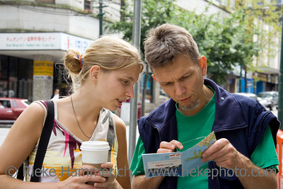 young woman and her father studying a city map - vancouver downtown