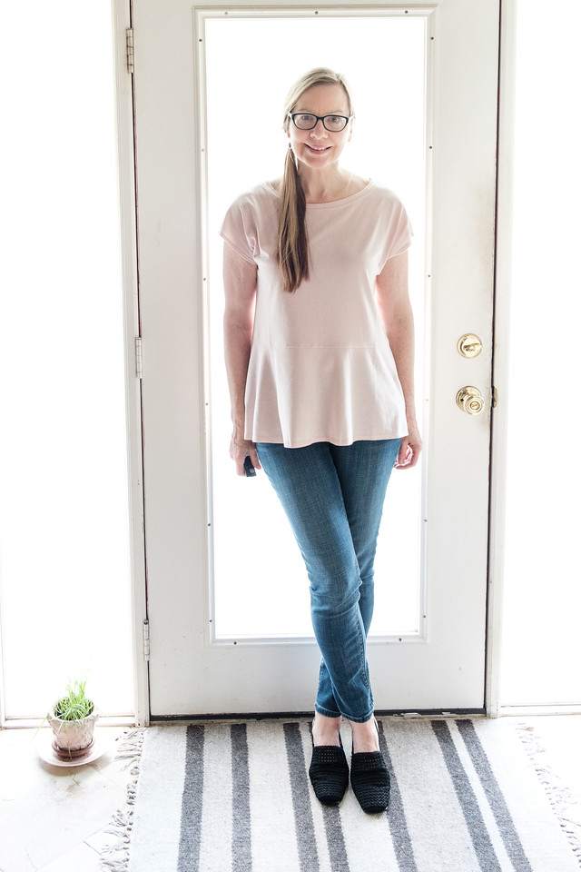 Woman standing in front of door in blush pink top, blue jeans and black slides