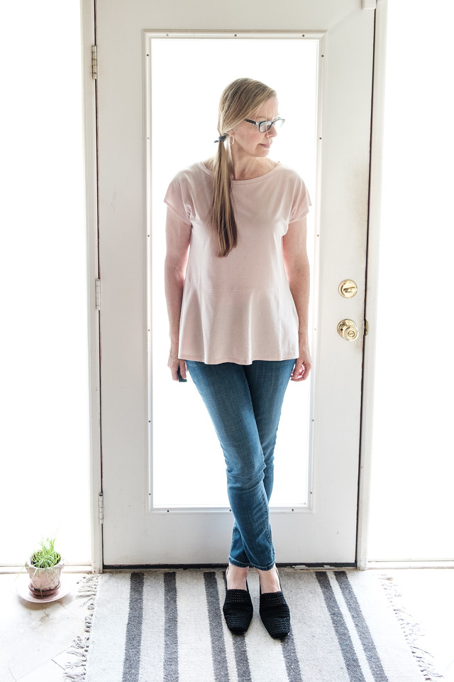 Woman standing in front of a door in a blush top, jeans, and black loafers