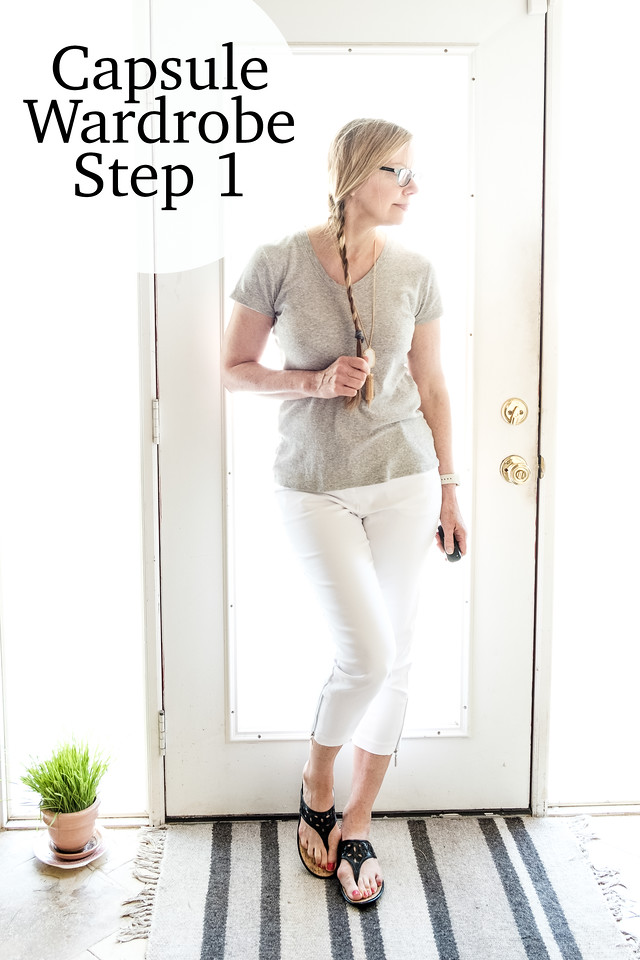woman in front of a door in white pants, gray t shirt
