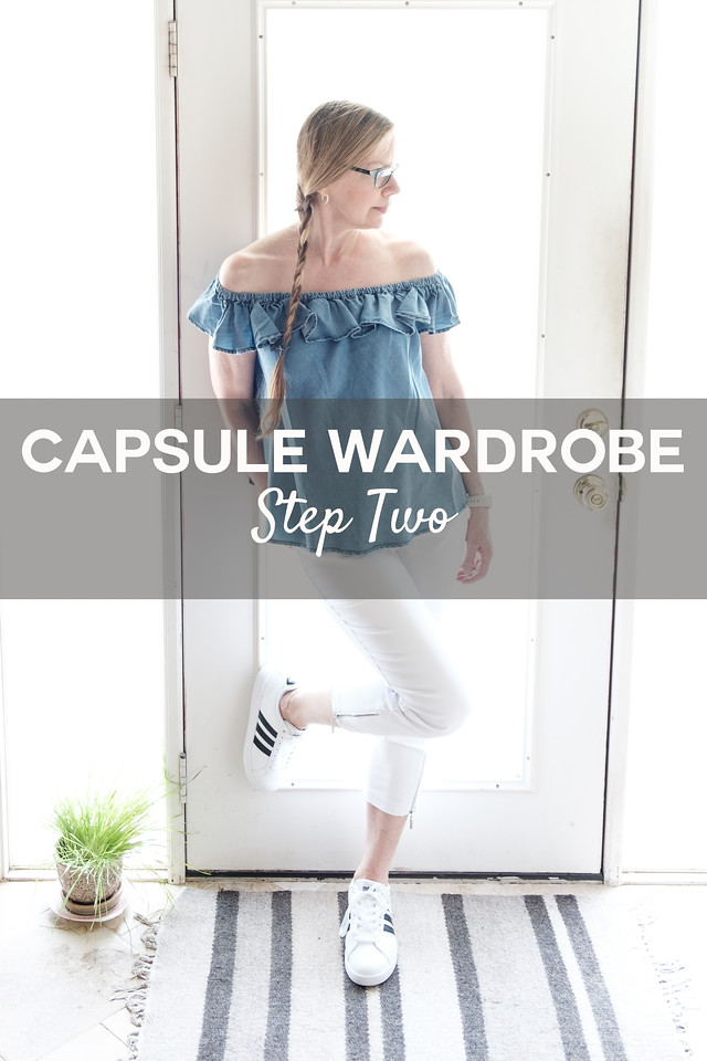 Woman in chambray and white in front of a door with the text overlay Capsule Wardrobe Step two
