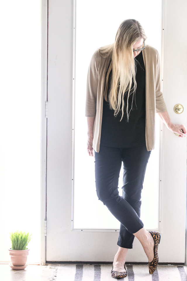 Woman in front of door with black pants, black shirt, beige sweater and leopard print flats.