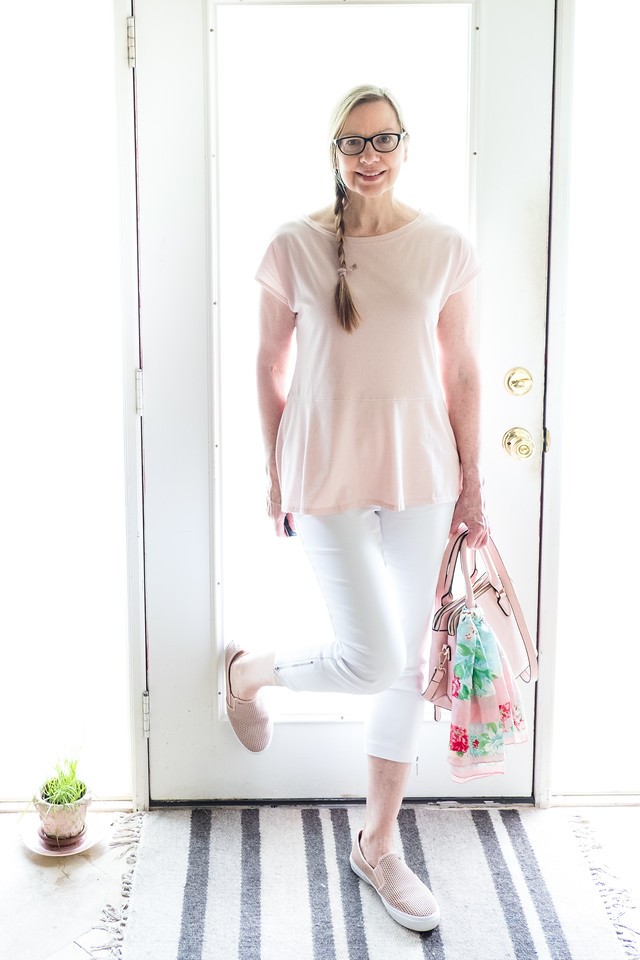Woman in blush shoes, purse and top with white skinny pants