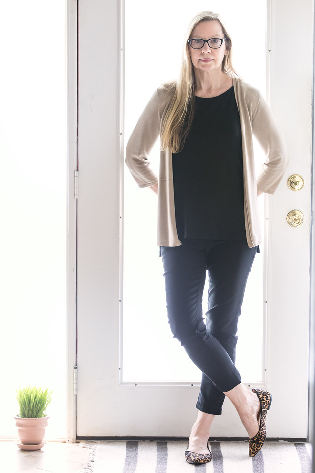 Woman in front of a door with black pants, black top, beige sweater and leopard print flats.