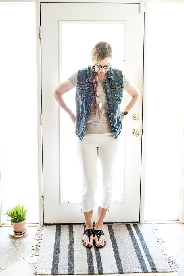 Woman wearing white jeans, gray t shirt and jeans vest