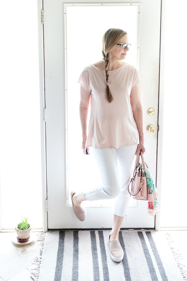 Woman wearing blush shoes, top and purse with white skinny pants