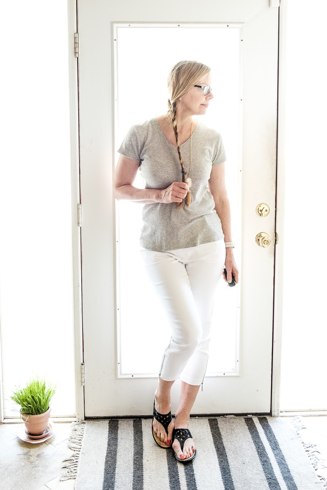 Woman in white pants, gray t shirt in front of a door