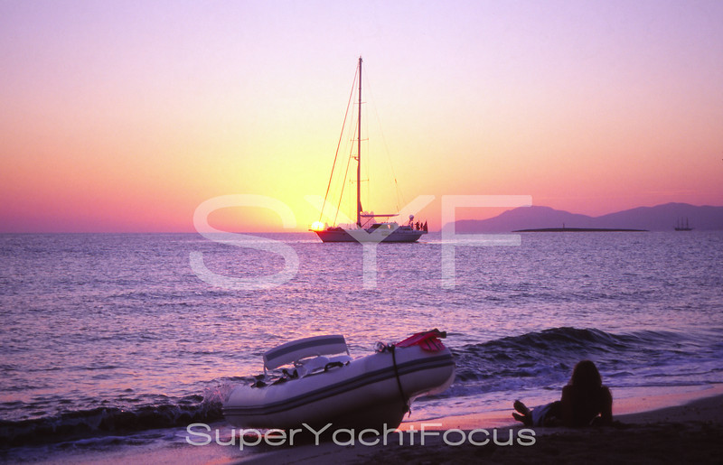 Sailing yacht at sunset with tender