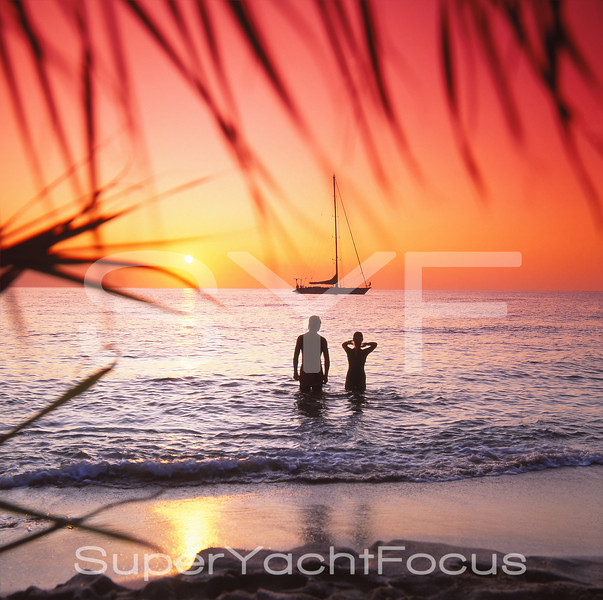 Couple at sunset with sailing yacht