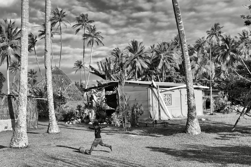 Enfant jouant au football devant sa maison à Luengoni. Lifou/Iles Loyauté/Nouvelle-Calédonie