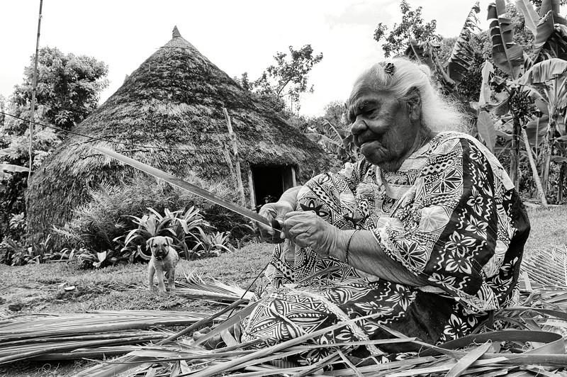 Joséphine Leanga Adrie préparant des feuilles destinées à être tressées devant sa maison de la tribu de Hnathalo. Lifou/Iles Loyauté/Nouvelle-Calédonie