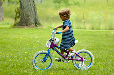 Stock image of a young girl on a bicycle with training wheels