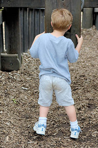 Stock image of a young boy at the playground looking through a periscope