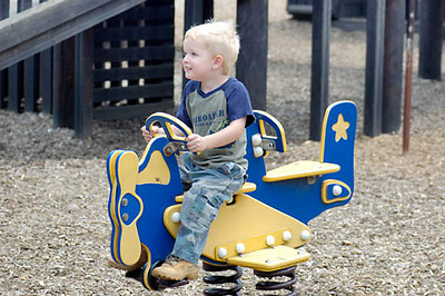 Stock image of a young blonde boy on a bouncing airplane at the playground
