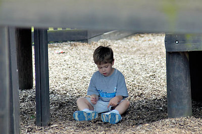 Stock image of a young boy at the playground sitting alone under the walkway