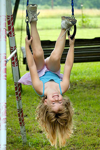 Stock image of young girl hanging upside down on a swing set