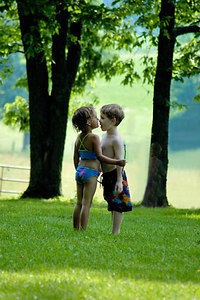 Stock image of a young boy and girl closely facing each other to see who is the tallest