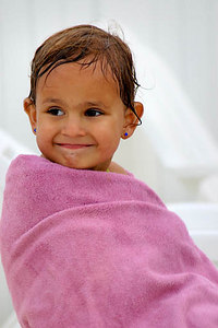 Stock image of a very young brown eyed girl with a captivating smile and wrapped in a pink towel